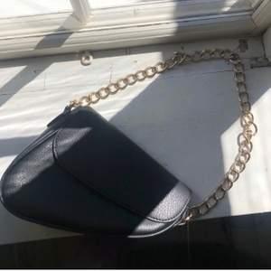 Säljer denna svarta axelväska med guldetaljer. Lagom stor väska