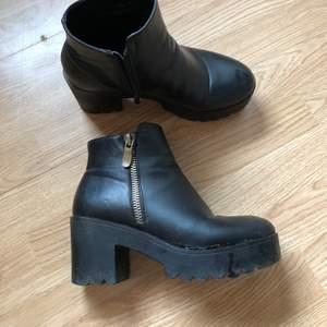 högklackade skor i svart syntetiskt läder med bred klack och både riktig dragkedja + fejk dragkedja som detalj. storlek 39 men är lite stora i storleken. använt skick men inga direkt synliga slitningar, kommer rengöras ordentligt innan du får dem.