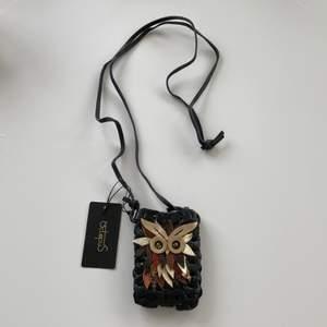 Helt nytt äkta skinnfodral/miniväska i danska märket octopus . Aldrig använt, helt nytt!!  Inköpt för 399kr passar till ha mindre mobil i, liten plånbok, nycklar etc. Kan skickas mot fraktkostnad 44kr
