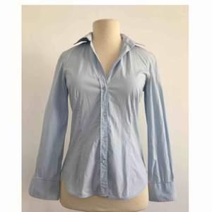 Skjorta i slimfit-modell.  Märke: Zara Basic Storlek: XS Skick: Mycket gott. Använd endast en gång. Pris: 100 kronor eller bud. Frakt: Betalas av köparen.