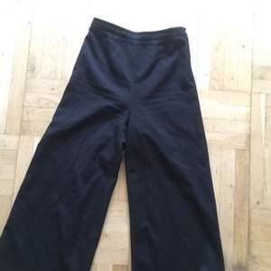 Svarta kostymbyxor, supertighta i midjan men med utsvänga ben, fina till klackar!