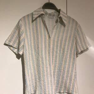 Figursydd skjorta i fina pastellfärger. Kan hämtas upp i Lund, om du vill ha den hemskickad tillkommer frakt.