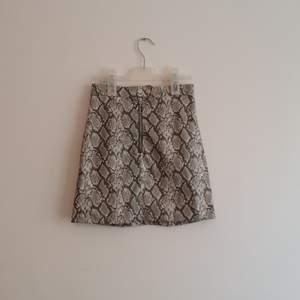 Mönstrad kjol i läderimitation. Storlek 32.  Frakt tillkommer.