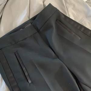 Svarta kostymbyxor med samets fickor och rand på vardera ben. Byxorna kommer ifrån zara och har använts ett fåtal gånger. Strl XS och passar mig på 175cm. Fickorna på sidorna är låtsas och går er att använda. Hör gärna av dig vid intresse!