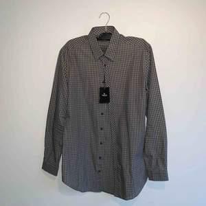 Gråsvart slim fit / long line skjorta från Tiger Of Sweden. Aldrig använd endast provad med prislapp kvar på.  Skick 10 / 10. Ord pris 999kr.