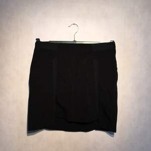 Svart kjol med detaljer och ett lite kortare framstycke från H&M.