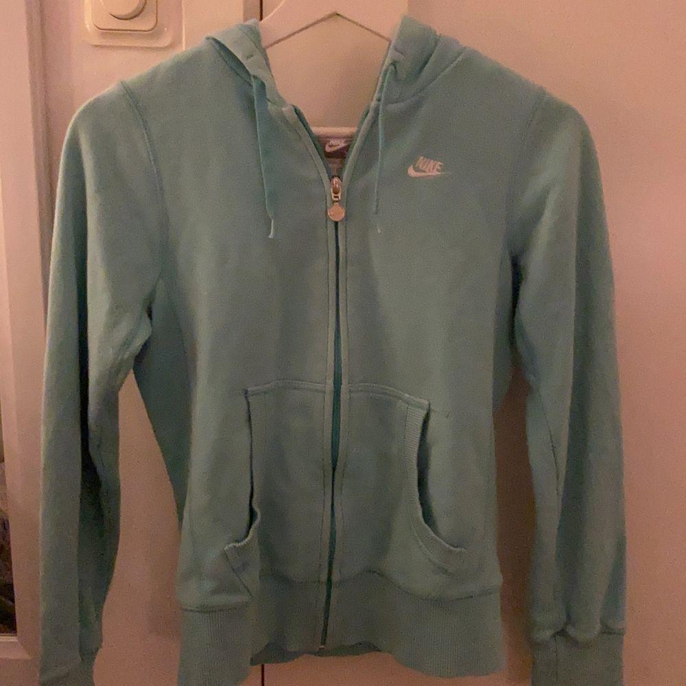 Jag säljer denna blåa Nike zipper hoodie eftersom den inte kommer till användning längre men den är i nästan nyskick, den är ÄKTA. Den är lite oversized och lång så passar mellan storlekarna xs-m. Om någon har några andra frågor hör bara av er!💞💞💞. Huvtröjor & Träningströjor.
