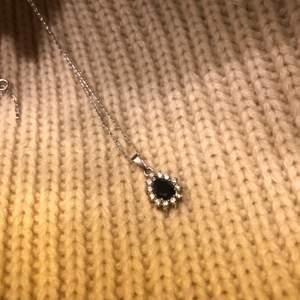 Halsband i silver med ett hängsmyckr med blå detalj.