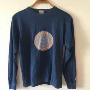Stormy Blue/Pharrows vintage långarmad tröja i navy. Snyggt orange print på bröstkorgen och ärmen. Sitter väldigt fittad, japansk modell.