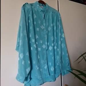 Cool vintageblus i ljusblått, silkeslikt material. Passar de flesta storlekar beroende på hur man vill ha den. Snygg som oversize och/eller att ha nerstoppad i byxor.