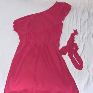 Rosa enaxlad klänning med volanger, band att knyta runt midjan eller på axeln som på bilden tillkommer.