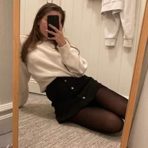 """Kort svart skjol i mockaliknande material med knappar som """"håller ihop"""" kjolen. Väldigt skön och bra kvalite men använder den inte längre. Jag är 160 och petit i kroppen, kjolen är så lång som på bilderna. Köparen står för frakt (vet ej det fraktpriset ännu)"""