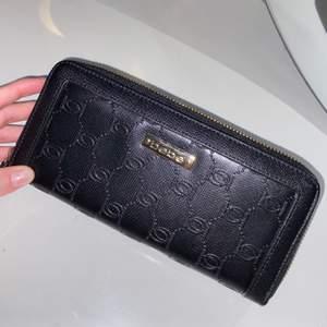 Svart plånbok från märket Bebe med guldiga detaljer. Flertal kortfack & mynthållre med extra dragkedja! Aldrig använd, frakt ingår.