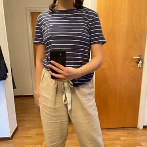 """En Polo Ralph Lauren T-shirt i storlek S. Det är egentligen en """"herr"""" T-shirt men den funkar ju för alla. Den är blå och vit randig med grön Ralph Lauren logga!!:)"""