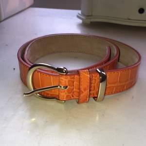 jättefint bälte i hög kvalitet med orange krokodilmönster och gulddetaljer, knappt använt pga för stor storlek