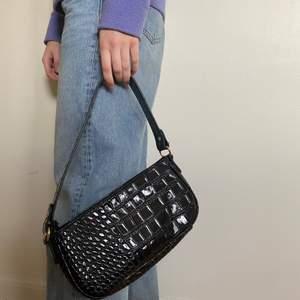 En svart orm mönstrad baguette väska 💖😊 den är använd ett fåtal gånger och det är i väldigt fint skick💖🥳👏❤️