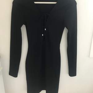 En svart tajt klänning från Gina Tricot med snörning vid brösten, bara använd några gånger.                           Köparen står för frakten!