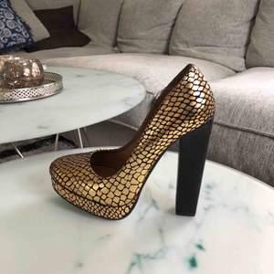 Guld- och svartmönstrade klackar med platå i storlek 39. Endast använda en gång. Möts upp i Stockholm eller så står köparen för frakten 😁