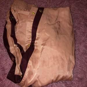 Det är ett par rosa byxor med knappar på sidan ser lik den som på bilden bara att den har röd streck har aldrig använt dom köpebdom för 2 år sedan för 600 kr❤️
