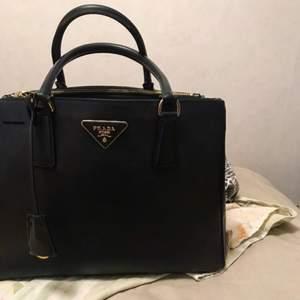 Svart Prada saffiano väska i läder. En riktigt elegant lyxig väska. Köpt för 3200kr. Först till kvarn. För mer detaljer skicka ett meddelande.