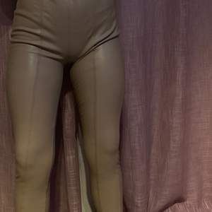 Läderbyxor med resårband i midjan och detaljer på benen. Aldrig använda förutom till bilden! Stretchigt material och töjs ut efter ens kroppstyp. Storlek 34. Pris: 90 kr +frakt