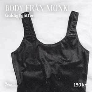Mjuk, sammets-aktig, svart body med guldigt glitter från Monki. Använd 1 gång. I nyskick! Stl: XS. Köparen står för frakt!