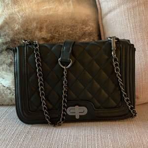 Svart klassisk handväska med metallgrå kedja, köpt på bubbleroom för många år sen. Kommer inte till användning, säljs därför till ett lågt pris