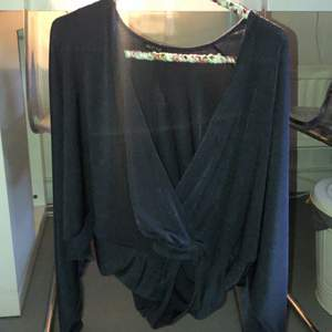 Glittrig blouse v-ringad i polyester från nelly