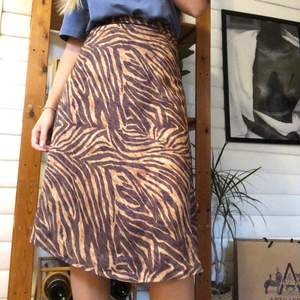 Vadlång kjol med dragkedjeknäppning baktill.