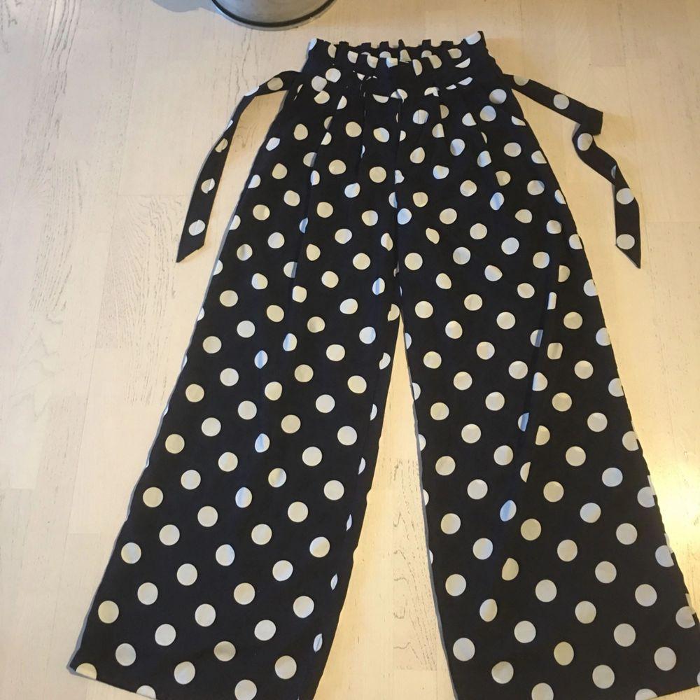 Mörkblåa byxor med vita prickar.  Använda 1 gång. Ens knäppet lite löst men går enkelt att lösa med ett egen gjort stygn. Samma avslappnade passform som byxor från weekday. Jeans & Byxor.