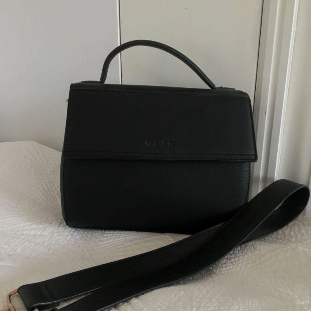 Väska i svart fakeläder från NA-KD med avtagbart axelband. Toppenskick då den aldrig har använts! Nypris 499. Väskor.