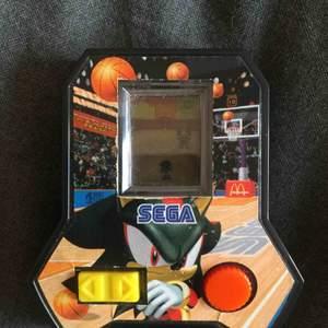 """SEGA, SONIC THE HEDGEHOG spel man fick i Happy Meal 2006 (Sverige). Ett """"svartvitt"""" pixlat spel där man spelar som karaktären Sonic the hedgehog och kastar basketbollar mot """"motståndarna"""". Tar fram extremt mycket nostalgikänslor!"""