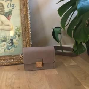 Så otroligt söt liten axelremsväska som jag köpte på åhléns för några år sedan men har tyvärr aldrig hittat något tillfälle att använda den. Bra kvalitet och fin beige färg med gulddetaljer. Köpt för ca 300kr