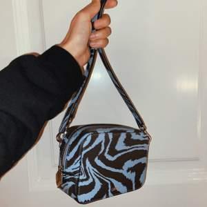 Axelremsväska från Ganni i mönstrat skinn. Köpt förra året och endast använd en gång. Superfint skick men säljer då den inte kommer till användning 💙