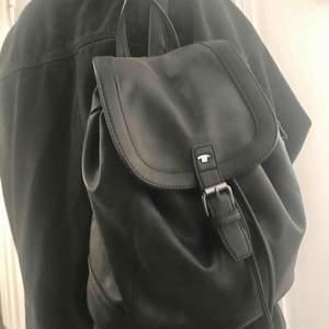 """Snygg ryggsäck i fuskskinn, fint skick! Reglerbara axelband och dragsko under väskans """"lock"""". Dragkedjan på innerfacket har typ hoppat ur och går inte att stänga men inga problem att ordna för den som orkar.  Ca 34 x 28 cm :)"""