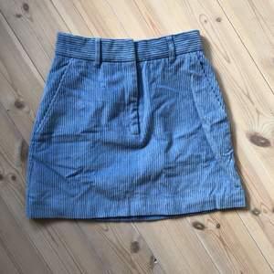 Ljusblå, kort manchesterkjol från H&M Trend. Dragkedja, dold knapphake och fickor på sidorna! Mkt sparsamt använd.