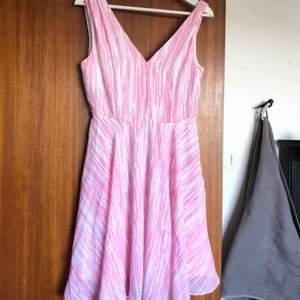 Somrig klänning i vitt och rosa mönster💕  Kort modell med en fin V-ringning både bak och fram. Använd en gång på skolanvslutning💞