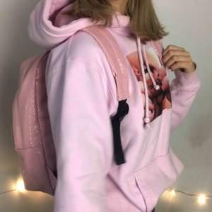 Rosa ryggsäck med blank yta och gulligt mönster. ALDRIG ANVÄND, säljer pga att jag redan har en liknande. Väskan rymmer mycket och får plats med dator, skolböcker osv