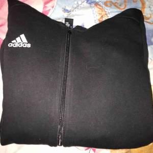 Svart hoodie från Adidas med vitt tryck på ärmen. Använd cirka två gånger. Köparen står för frakt!