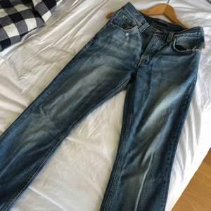 Raka blåa nudie jeans med snygga slitningar vid fickor och najs tvätt.