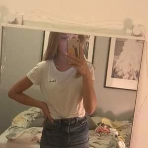 En enkel vit t-shirt med text i hörnet från hm i storlek S. Säljer för 40kr
