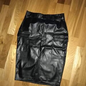 Oanvänd kjol i skinnimitation från nelly. Två fickor framtill. Knälång på mig