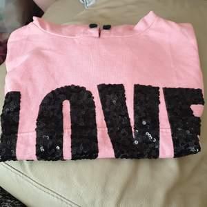 Fin rosa huvtröja med texten Love i svarta paljetter. Mycket fint skick.skick.storlek 1146/152