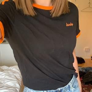 """Svart T-shirt från NA-KD med neonorange detaljer. På bröstet står det i liten text """"Lovely"""". Använd ett fåtal gånger, fint skick. Köpare betalar frakt! 🧡"""