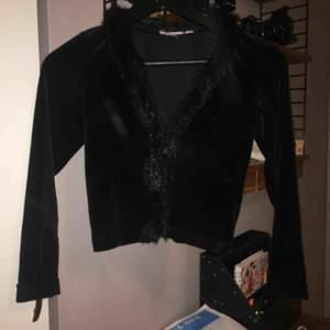 Snygg tröja med knäppning. Den är gjort av sammet och låtsas päls.