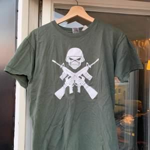 Militärgrön tshirt med vitt tryck och text på ryggen
