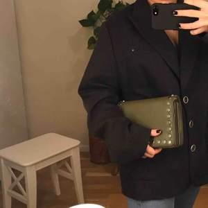Militärgrön axelbandsväska med silvriga metallprickar längsmed kanterna. På väskans ena kant är färgen lite uppskrapad men det syns knappt (vid intresse skickas fler bilder privat). Möts i Stockholm annars står köparen för frakten🐍🌳🌱