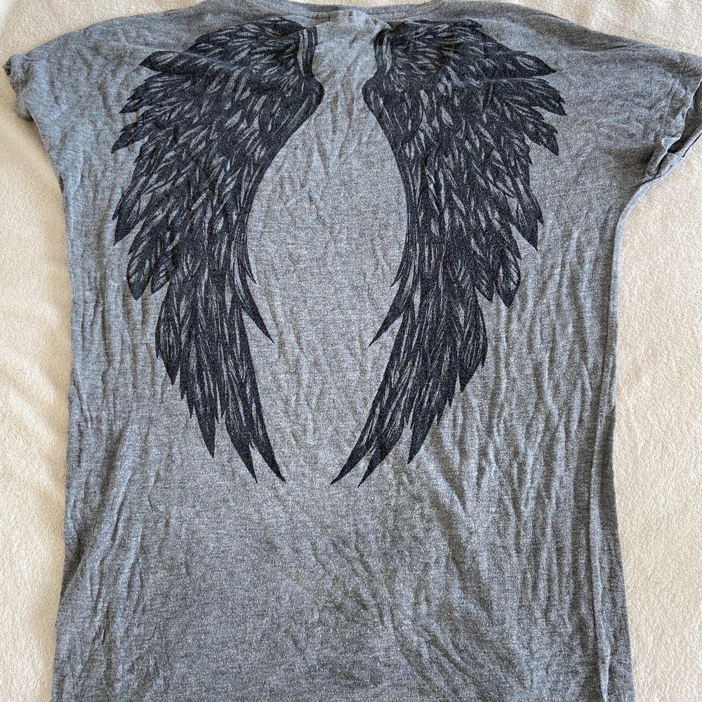 Grå t-shirt med svarta vingar där bak. Stor i storleken och väldigt pösig. Är gjord i 95% viskos och 5% elastan.. T-shirts.