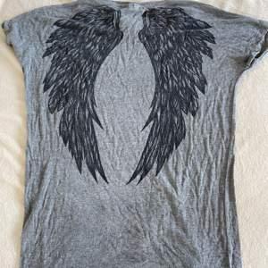 Grå t-shirt med svarta vingar där bak. Stor i storleken och väldigt pösig. Är gjord i 95% viskos och 5% elastan.