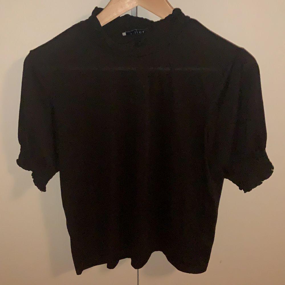 Svart T-shirt med fina detaljer runt hals o armar. Aldrig använd o är i bra skick . T-shirts.